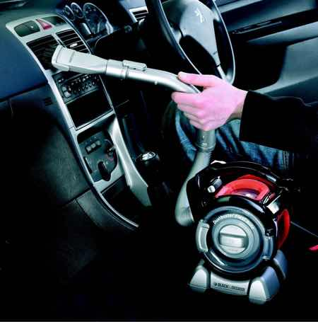 picture of a man vacuuming his car