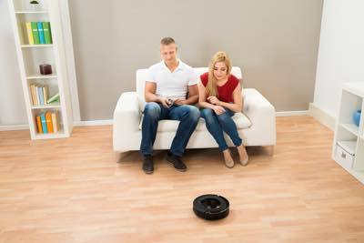 couple watching their robot hoover