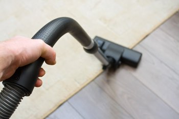 Picture showing a cylinder vacuum on the edge of a carpet and hard wood floor
